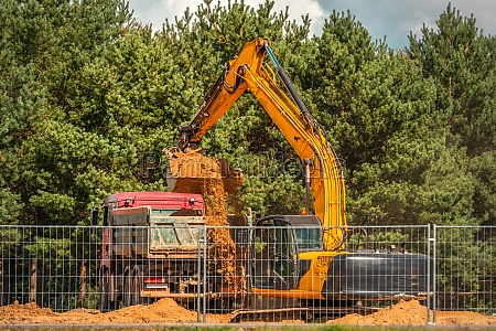 excavator loading sand in rear end
