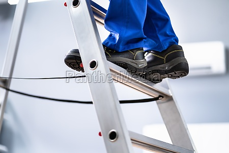 man in shoes climbing step ladder