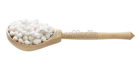raw tapioca pearls in wooden spoon