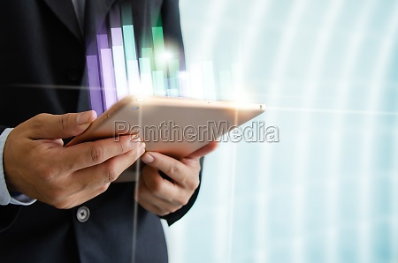 businessman holding tablet and graph financial