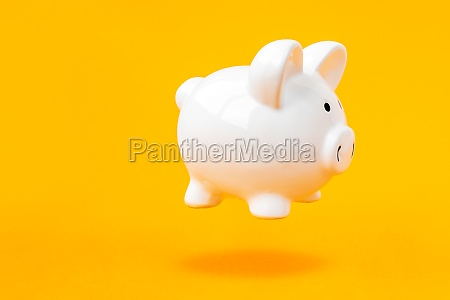 piggy bank levitating over a yellow