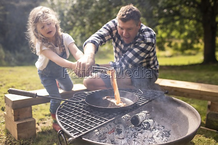father and daughter cooking bacon over