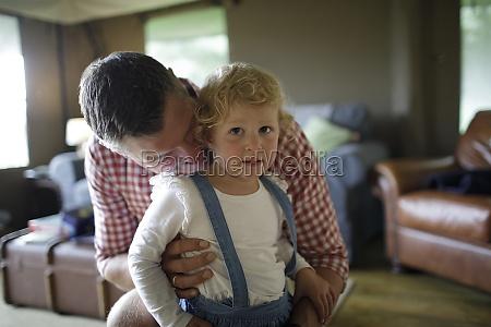 portrait affectionate father hugging toddler daughter