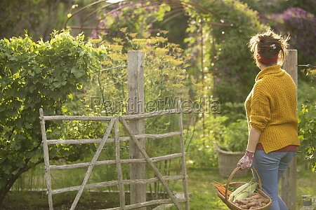 woman with fresh harvested vegetables at