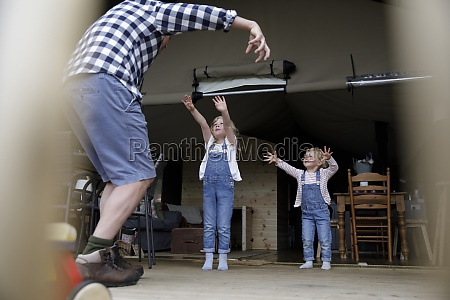 playful father and daughters on cabin