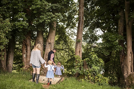 family holding hands walking among trees