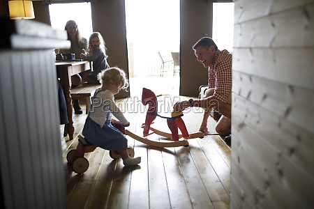 family plying with rocking horse and