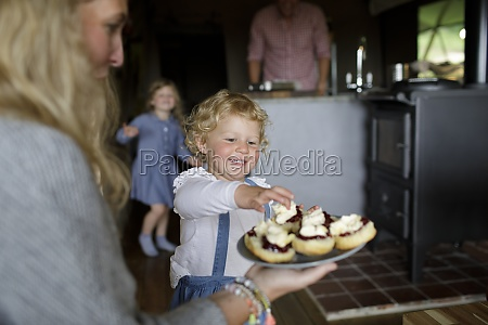 eager girl reaching for biscuit with