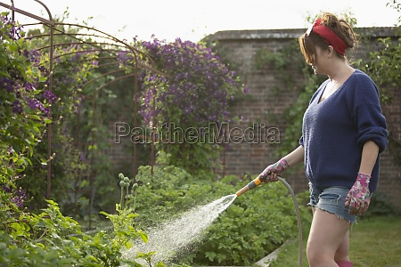 woman with hose watering vegetables in