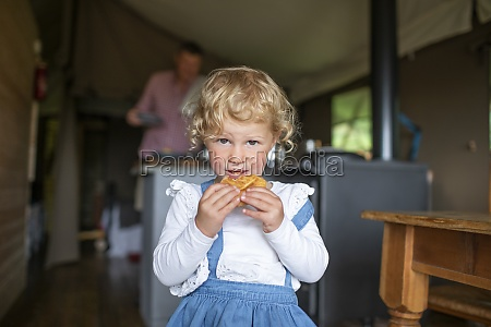 portrait cute girl eating biscuit in