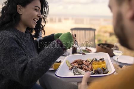 couple enjoying seafood lunch on patio