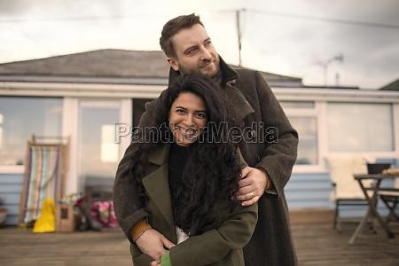 portrait happy couple in winter coats