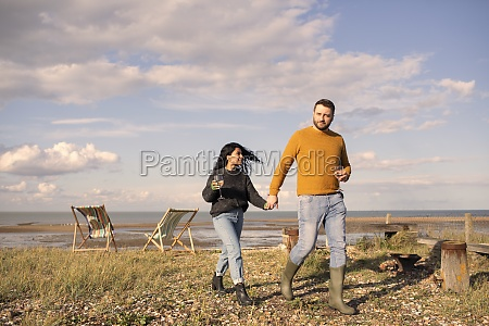 happy couple with wine holding hands
