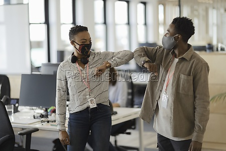 business people in face masks elbow