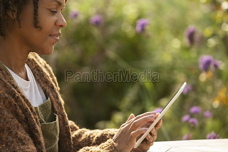 woman using digital tablet in sunny