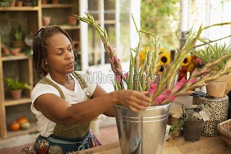 female florist arranging flowers in bucket