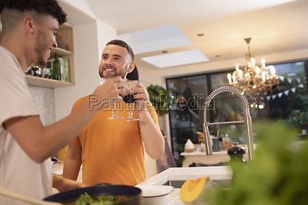 happy gay male couple drinking wine