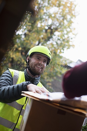 friendly delivery man in helmet delivering