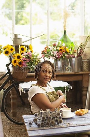 portrait confident female florist taking coffee