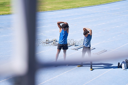 male runners stretching on sunny blue