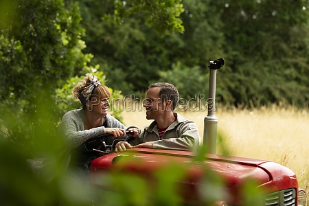 happy couple talking at tractor in