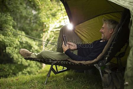 man in camping lounge chair fishing