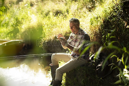 man fly fishing and using smart