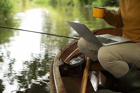 man fly fishing and using laptop