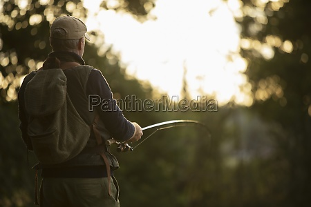 man with backpack fly fishing