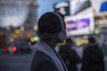 young woman in headphones on city