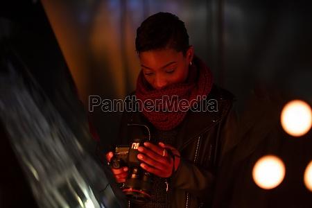 young woman with camera at dark