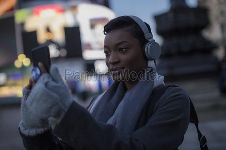 young woman in headphones taking selfie