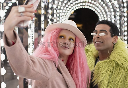 eccentric fashionable couple taking selfie under