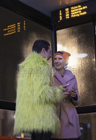 stylish young couple waiting at bus