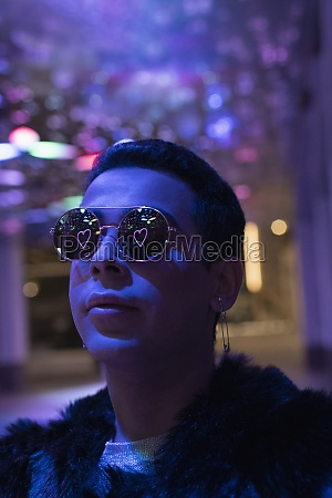reflection of neon heart in sunglasses