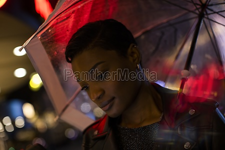 young woman under umbrella and neon