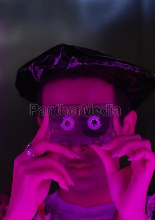 portrait stylish young man holding cassette