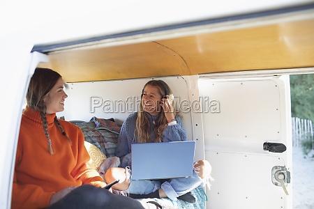 happy young women friends using laptop