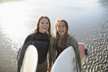 portrait happy young female surfers with