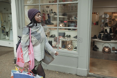 young woman with shopping bags outside