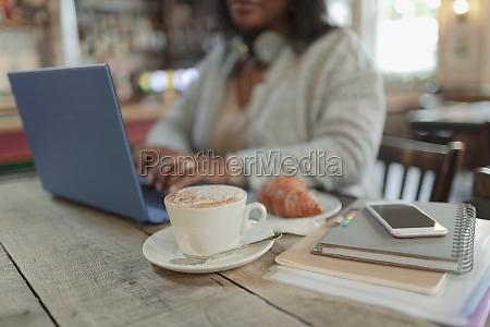 woman working at laptop next to