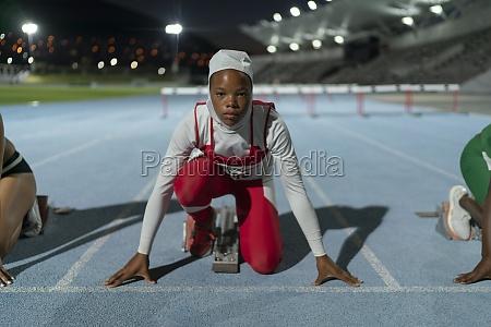 portrait determined female runner in hijab