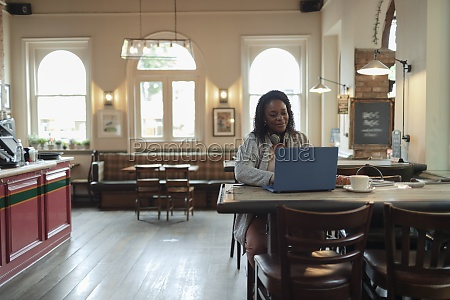 businesswoman working at laptop at cafe