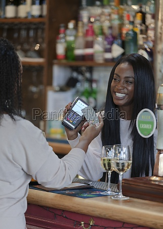customer paying female bartender with smart