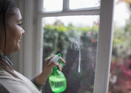 woman cleaning windows with glass cleaner