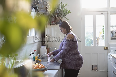 woman doing dishes at kitchen sink