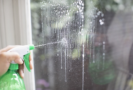 close up cleaning window with spray