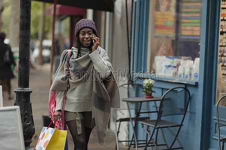 young woman with shopping bag talking