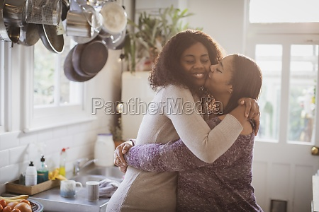 mother and daughter hugging and kissing