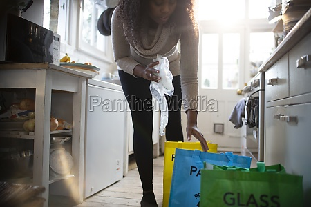 woman sorting recycling into bags on